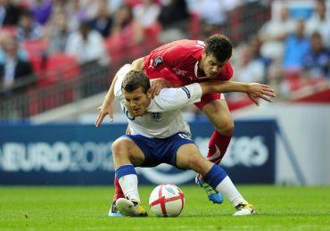 Wilshere (depan) turut beraksi bersama England pada pusingan kelayakan Euro menentang Switzerland tahun lalu.