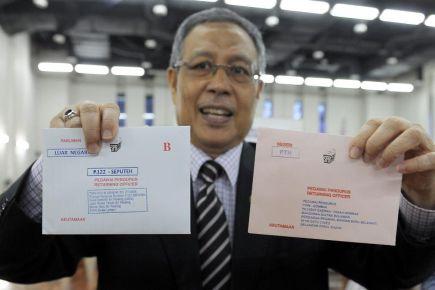 Pengerusi Suruhanjaya Pilihan Raya (SPR), Tan Sri Abdul Aziz Mohd Yusof menunjukkan surat berisi kertas undi pos bagi P.122 Parlimen Seputeh dari Dublin, Ireland pada majlis penerimaan balik kertas undi pos luar negara di Kementerian Luar di Putrajaya pada Khamis. -Foto BERNAMA