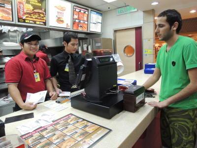 Ahmed (kanan) berbual dengan pekerja-pekerja di premis makanan segera di ruang transit KLIA yang telah menjadi rakannya sejak dia terkandas di situ lebih dari 50 hari. -foto T.SELVA/The Star