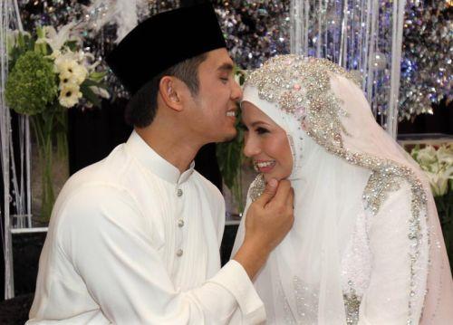 Irma dikucup oleh suaminya Redza Syah Azmeer selepas majlis pernikahan mereka, petang Jumaat. - Foto MOHD SAHAR MISNI