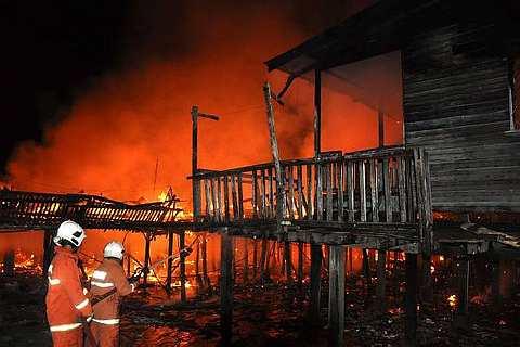 Anggota Bomba dan Penyelamat bertungkus lumus memadamkan kebakaran di Kampung Titingan, dekat Tawau lewat tengah malam tadi yang menyebabkan kira-kira 100 orang tinggal sehelai sepinggang. - Foto BERNAMA