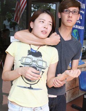 Lee (kanan) menunjukkan demonstrasi bagaimana perompak menyerang teman wanitanya sewaktu kejadian rompakan itu.