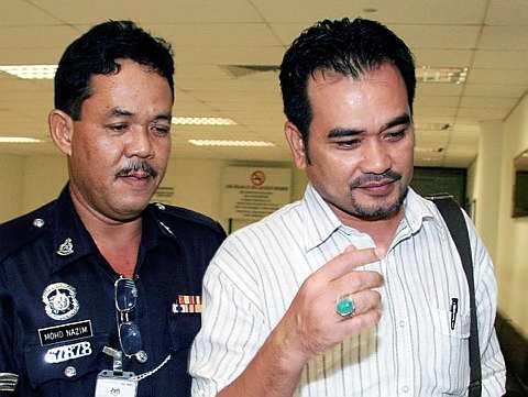 etua UMNO Bahagian Pandan dan anggota Jawatankuasa Tender Majlis Perbandaran Ampang Jaya, Abd Ghani Ismail (kanan) diiringi polis untuk menghadapi pertuduhan rasuah di Mahkamah Sesyen di sini hari ini.--fotoBERNAMA