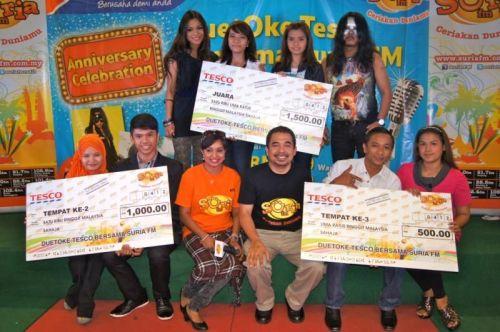 Para pemenang pada pertandingan karaoke Suria FM di Tesco Melaka bersama penyampai Kenchana Devi (tiga, kiri) dan Pengurus Operasi Suria FM, Subarma Mokhtar atau Subi (tiga, kanan).