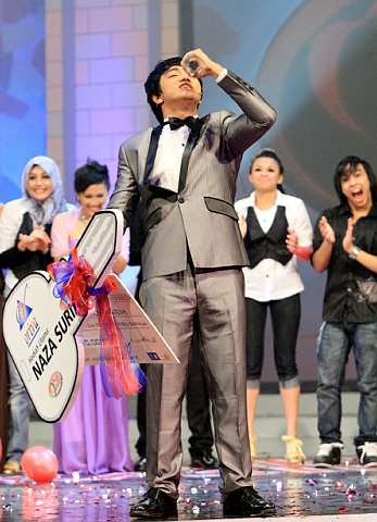 Muhammad Iqbal Mazlan mencium trofinya selepas diumumkan sebagai juara Pilih Kasih musim pertama. - foto THE STAR oleh DARRAN TAN