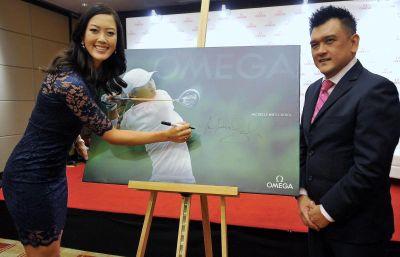 Michelle Wie (kiri) menurunkan tandatangan di atas gambar selepas selesai sesi pengenalan pemain di Kuala Lumpur, Isnin. Foto BERNAMA