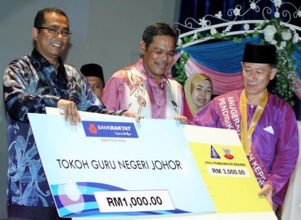 Menteri Besar Johor Datuk Seri Mohamed Khaled Nordin (kiri) menyampaikan replika cek kepada bekas Pengetua Maktab Sultan Abu Bakar, Zulkipli Mahmud, 60, yang dinobatkan sebagai Tokoh Kepimpinan sempena Perayaan Hari Guru Peringkat Negeri Johor di Pusat Islam Iskandar Johor di Johor Bharu pada Sabtu. Turut kelihatan Pengarah Pelajaran Johor Mohd Nor A. Ghani (tengah). -Foto BERNAMA