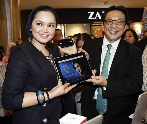 Penyanyi Datuk Siti Nurhaliza bersama produk terbarunya iPad dan peranti Yes Huddle 4G sambil diperhatikan Pengarah Urusan YTL Corporation Bhd juga Pengerusi Eksekutif YTL Communications Sdn Bhd, Tan Sri (Dr.) Francis Yeoh di butik Yes, Lot 10, Kuala Lumpur.