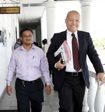 Riduan Masmud (kiri) bersama peguamnya, Loretto S.Padua (kanan) berjalan keluar dari mahkamah sesyen di Kota Kinabalu pada Isnin. Foto NORMIMIE DIUN / THE STAR