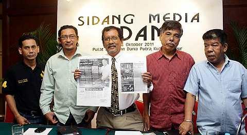 Mokhtar (tengah) menunjukkan keratan akhbar kenyataan GAFIM berhubung perletakan jawatan Mat London (paling kanan) pada sidang media tergempar di Pusat Dagangan Dunia Putra (PWTC), Selasa. Turut hadir Pemangku Timbalan Presiden FDAM, Syed Zulkifli Syed Masir (dua dari kiri) dan AJK Biro Disiplin dan Perundangan FDAM, Rahim Bujang (dua dari kanan). Foto THE STAR Oleh ELLIS KHAN.