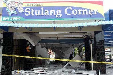 Seorang anggota Polis dari Unit Forensik mencari bahan bukti di tapak sebuah restoran
