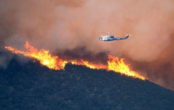 Sebuah helikopter menjatuhkan bom air bagi menghalang kebakaran daripada terus merebak.