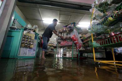 Peniaga kedai runcit, Asmadi Harun, 40, menyelamatkan barang-barang selepas kedainya dinaiki air akibat hujan berterusan sejak beberapa hari lepas di Kampung Cherating Baru, Kuantan pada Rabu.