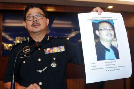 Datuk Ku Chin Wah memegang gambar suspek di ibu pejabat polis kontigen Kuala Lumpur pada Selasa. -Foto BERNAMA.