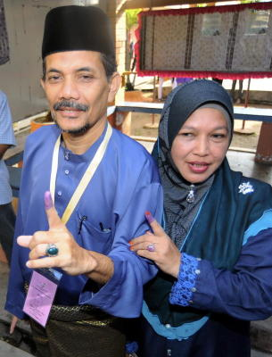 Calon Barisan Nasional Dewan Undangan Negeri (DUN) N20 Sungai Limau, Dr Ahmad Sohaimi Lazim (kiri) dan isterinya Siti Bunga Ismail menunjukan kesan dakwat kekal selepas mengundi bagi Pilihan Raya Kecil DUN Sungai Limau di Sekolah Kebangsaan Dulang di Yan, Kedah, Isnin. -fotoBERNAMA
