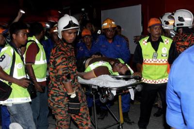 Seorang ahli keluarga pengsan setelah mengeluarkan mayat mangsa yang terperangkap dalam runtuhan penyambung susur keluar Jambatan Kedua Pulau Pinang di Lebuhraya Tun Dr Lim Chong Eu di Batu Maung, Jumaat. -fotoBERNAMA