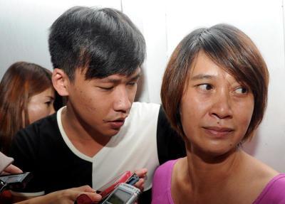 Isteri mangsa Lee Chai Song, 48, (kanan) berada di kawasan runtuhan penebat kilat Menara Umno di Jalan Macalister setelah suaminya dipercayai tertimbus dalam lubang jalan sedalam lima meter.-fotoBERNAMA