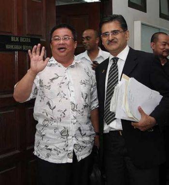 DIDAKWA... Bekas Ahli Parlimen Labuan, Datuk Suhaili Abdul Rahman (kiri) dengan diiringi peguamnya, Rakbir Singh melambaikan tangan sebaik keluar dari kamar Mahkamah Sesyen Kota Kinabalu selepas dikenakan pertuduhan petang tadi.