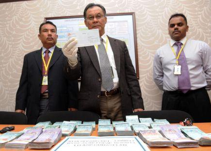 Ketua Jabatan Siasatan Jenayah Narkotik (JSJN) Perak, Asisten Komisioner Roslan Abdul Wahid menunjukkan sekeping cek bernilai lebih RM50 ribu pada sidang media di Ibu Pejabat Polis Kontinjen (IPK) Perak di Ipoh pada Rabu. Pada 16 November Jabatan Siasatan Jenayah Narkotik IPK Perak telah menangkap seorang lelaki dan merampas serta menyita sejumlah wang tunai dan beberapa buah kenderaan serta dua buah rumah milik suspek yang dianggarkan berjumlah RM1,216,806.33. -Foto BERNAMA