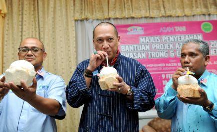 Menteri di Jabatan Perdana Menteri Datuk Seri Mohamed Nazri Abdul Aziz mencuba keenakan air kelapa muda ketika hadir pada program penyampaian Bantuan Azam Tani (fasa1) di Seratak Anjung Resort, Kuala Terong di Taiping, pada Sabtu.Turut hadir Adun Terong Datuk Rosli Husin (kanan) dan Pengarah Mardi Perak Dr Zabri Abd Wahid (kiri).-Foto BERNAMA