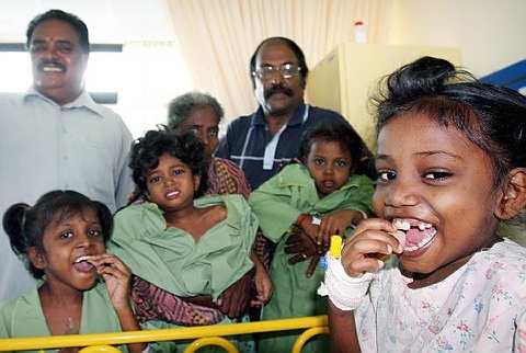 Yogeswary (kiri) dan sepupu Vikneswary (kanan) serta dua adik perempuannya, Ganggademi (tengah) dan Nageswari (dua, kanan) bersama nenek mereka N. Bathumalai, 61 (kiri, belakang), Penolong Setiausaha MIC Bahagian Jerai, A.P Muniandy (kiri, belakang) dan Supramaniam. Empat kanak-kanak perempuan berkenaan dimasukkan ke hospital apabila salah seorang daripada mereka dalam keadaan lemah selepas memakan tanah. Foto G.C. Tan / The Star