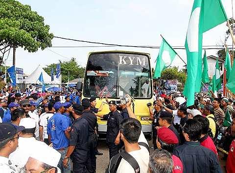 Sebuah bas yang membawa pelajar-pelajar dari Kolej Yayasan Melaka menjadi tumpuan penyokong-penyokong Barisan Nasional (BN) dan PAS yang mendakwa membawa pengundi hantu dari dari luar Melaka. Setelah kedua-dua wakil dari BN dan PAS memeriksa bas tersebut, mereka dibenarkan melalui jalan tersebut kerana bas tersebut mahu menuju ke sebuah kem bina semangat yang terletak di berhampiran pusat pengundian di Sekolah Kebangsaan ChinChin. Kelihatan para penyokong kedua-dua parti politik mengerumuni bas tersebut berdekatan pusat pengundian Sekolah Kebangsaan ChinChin di Jasin, Ahad. - Foto BERNAMA