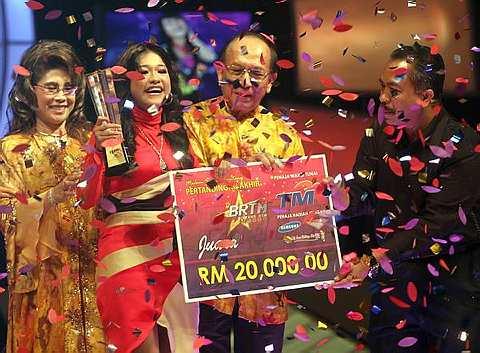 JUARA... Ernie menerima cek replika RM20,000 dan trofi daripada Datuk Seri Dr Rais Yatim sambil diperhatikan oleh isteri, Datin Seri Maznah Rais. - foto THE STAR oleh SAMUEL ONG