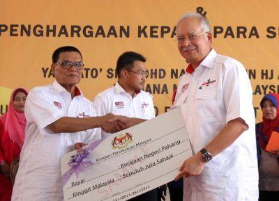 Najib menyerahkan cek tabung mangsa banjir berjumlah RM10 juta untuk kerajaan negeri Pahang yang diterima Menteri Besar Pahang, Datuk Seri Adnan Yaakob (dua, kiri) pada Majlis Penyerahan Bantuan Mangsa Banjir Peringkat Nasional dan perhargaan kepada para sukarelawan di Termeloh, Jumaat. Foto ONG HAN SEAN / THE STAR