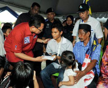 Mohd Puad menyampaikan sumbangan kepada Konstabel Mohammad Qaiyum (tengah) yang selamat pulang ke rumahnya di Kampung Bukit Kelicap, Batu Pahat, Johor. -fotoBERNAMA