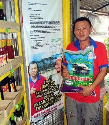 Pemilik pasar raya mini Tan Jai Wei, bersama beras jenama 'Kampungku' merupakan penganut agama Buddha yang berniaga sambil bersedekah termasuk untuk aktiviti-aktiviti Islam di Taman Kenari. - foto BERNAMA