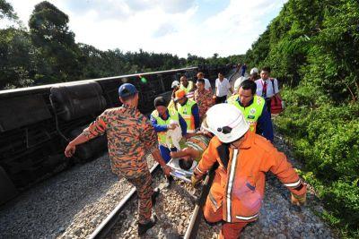 Pasukan bomba dan penyelamat mengeluarkan seorang mangsa yang cedera selepas sebahagian koc kereta api penumpang dari Kuala Lumpur ke Singapura tergelincir.