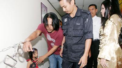 Badrul Muhayat Ahmad Jailani memegang anaknya, Siti Nor Batrisya sambila diperhatikan isteriya, Julia Daud di Mahkamah Majistret Ampang dekat Kuala Lumpur semalam. - Foto Ihsan UTUSAN