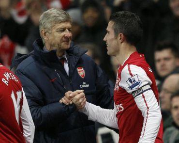 Wenger (kiri) bersalam dengan pemainnya, Robin van Persie selepas perlawanan menentang City, Isnin.