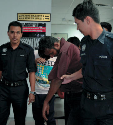 Penjual batu permata, K Sangelee Thevan, 38, (tengah) diiringi anggota polis keluar dari Mahkamah Majistret di Shah Alam, selepas menghadapi tuduhan menculik, mengurung dan menahan seorang budak lelaki berumur sembilan tahun yang juga anak kepada seorang bergelar