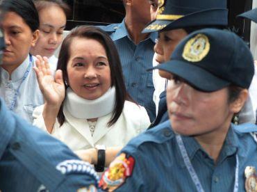 Arroyo (belakang, tengah) dikawal ketat oleh pengawal keselamatan ketika tiba di tiba di Mahkamah Passay City di selatan Manila pada Khamis.