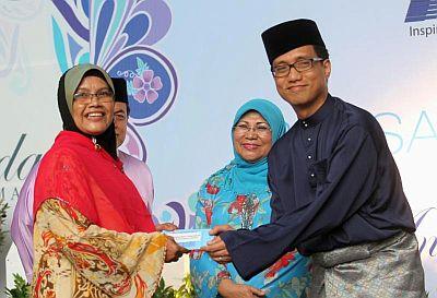 Ahmad Izham (kanan) menyampaikan sumbangan Tabung TV3 Bersamamu kepada salah seorang wakil pusat penjagaan rumah kebajikan sambil diperhatikan Rohani Karim.