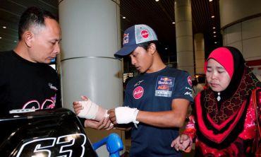 Zulfahmi (tengah) menunjukkan kedua-dua belah pergelangan tangannya yang berbalut kepada ayahnya, Khairuddin Weji (kiri) sambil diperhatikan oleh ibunya, Zarinah Parijan (kanan) sebaik tiba di Lapangan Terbang Antarabangsa Kuala Lumpur (KLIA) pada Khamis. Foto: BERNAMA