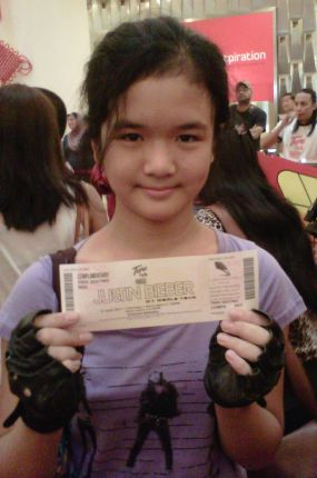 Cheah Suan Lyn memegang tiket pertama konsert Justin Bieber yang dimenanginya daripada Tune Talk di Bangsar Village 2, Kuala Lumpur, Sabtu. - Foto oleh SITI AZIRA