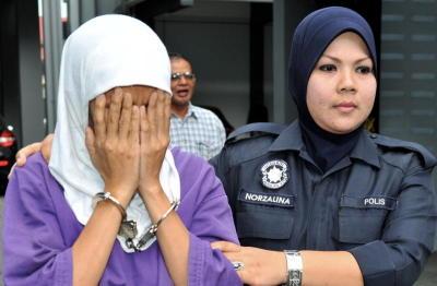 Pembantu rumah, Enong Nur Sukma, 41,(kiri), diiringi anggota polis, dihadapkan di Mahkamah Sesyen di Kota Baharu, Khamis, atas pertuduhan mendera anak majikannya yang berusia 15 bulan dalam satu kejadian pada Sabtu lalu. Enong yang berasal dari Bandung, Indonesia bagaimanapun mengaku tidak bersalah atas pertuduhan yang dibacakan terhadapnya oleh Hakim Mahkamah Sesyen Yusuf Yunus. -fotoBERNAMA