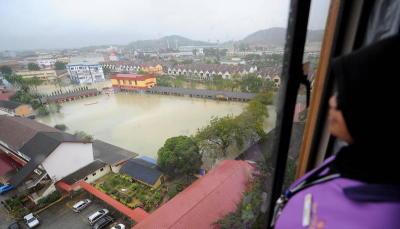 TENGGELAM… Kelihatan seorang kakitangan sebuah hotel Shiaha Salleh,48, melihat bandar Kuantan yang dilimpahi air banjir, Isnin. Banjir berlaku selepas hujan lebat dari malam Ahad dan mereka yang tinggal di kawasan banjir dinasihatkan supaya berjaga-jaga kerana hujan lebat dijangka akan berterusan sehingga 9 Januari depan. -fotoBERNAMA