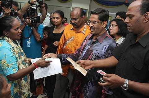 DATUK Dr S. Subramaniam dan Datuk M. Saravanan menjelaskan sesuatu kepada Alagi A Mayandi, 55 (kiri) yang memohon MyKad untuk ibunya pada kempen MyDaftar di Jabatan Pendaftaran Negara (JPN) Maju Junction di Kuala Lumpur, Sabtu. - Foto THE STAR/RAYMOND OOI