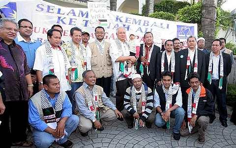 Najib bergambar sambil mendukung adik Nur Nuhasakinah Noorazman (tengah) pada majlis menyambut ketibaan wira-wira sukarelawan bantuan kemanusiaan ke Gaza di kediamannya di Jalan Duta, di sini hari ini. Turut kelihatan Anifah (empat, kiri) dan Noorazman (lima, kiri). Foto BERNAMA