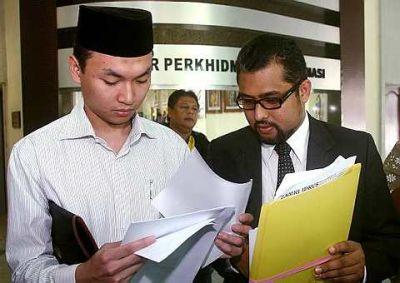 MOHD Saiful Bukhari Azlan (kiri) melihat beberapa dokumen bersama peguamnya, Zamri Idrus selepas memfailkan writ saman terhadap  penulis laman blog pahangdaily.com di Mahkamah Tinggi Shah Alam, hari ini.