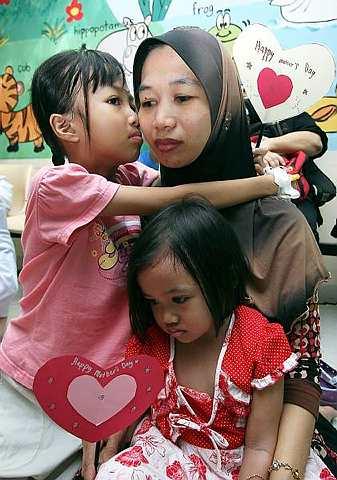 Faizna Syaferah Ismail (kiri) mencium dan memeluk erat ibunya Siti Rahmah Bana yang meriba Farisya Syazilla Ismail dalam satu majlis anjuran sebuah pertubuhan bukan kerajaan MySepakat sempena sambutan Hari Ibu di Institut Pediatrik Hospital Besar Kuala Lumpur, Sabtu. Program bertujuan menghargai jasa ibu yang tiada tolok banding pengorbanannya dan secara tidak langsung menceriakan kanak-kanak yang tidak bernasib baik di hospital ini. - Foto BERNAMA